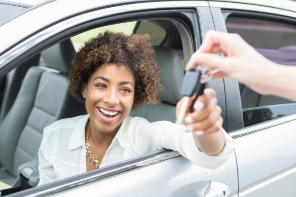 Jeune femme dans une voiture qui reçoit les clefs du véhicule en souriant