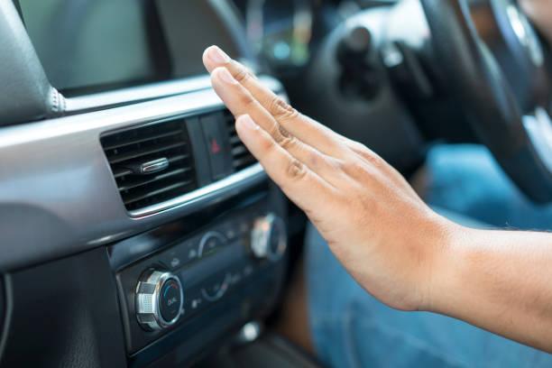 Main de femme devant le chauffage d'une voiture