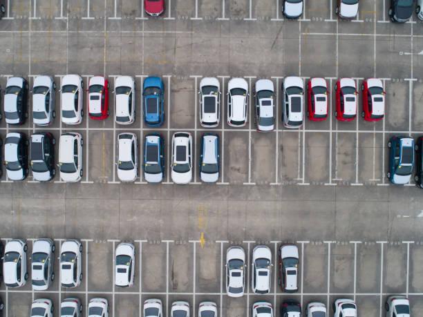 Parking avec plusieurs voitures d'occasion vues du ciel