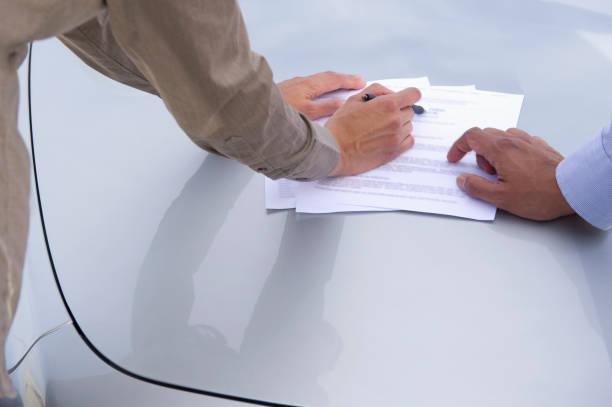 Deux personnes qui parcourent un document officiel sur le capot d'une voiture