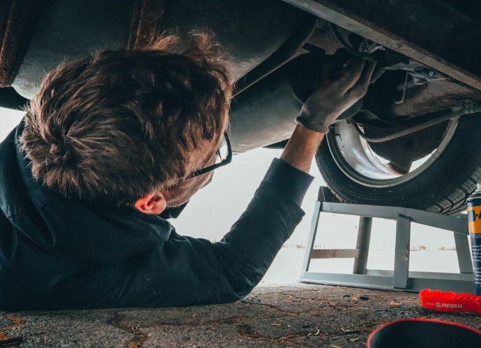 Homme qui est sous une voiture pour la réparer